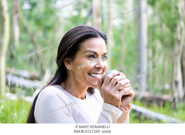 Hispanic woman having cup of coffee outdoors