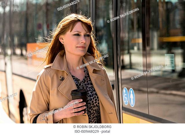 Woman with takeaway coffee next to city bus