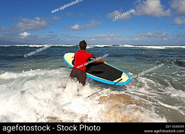 Man Surfer go to the water. Hoâ. . okipa Beach. Maui. Hawaii. One of the worldâ. . s best windsurfing beaches, Hookipa is also a favorite hangout for...