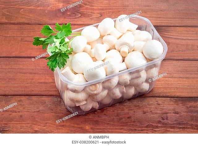 Fresh uncooked button mushrooms in a transparent plastic tray and sprig of parsley on a dark wooden surface