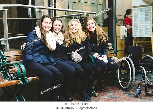 Teenage girls smiling on bench