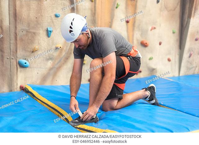 Wall climber putting on climbing shoes. Sport concept