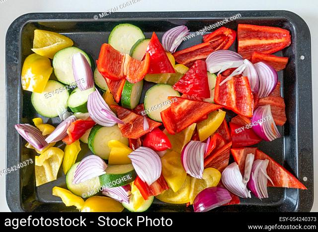 From above shot of prepared raw peppers, onions and courgettes on a roasting tray