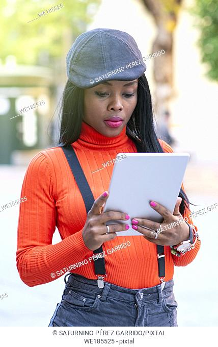Beautiful young woman with dark skin using a tablet in the middle of the street