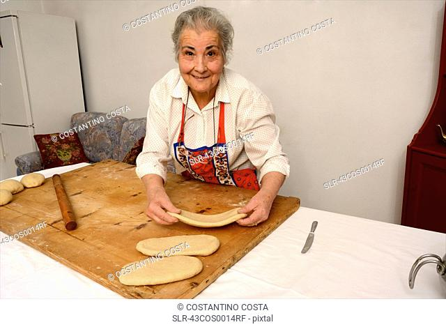 Older woman shaping dough on board