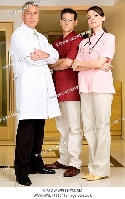 Portrait of a female doctor standing with two male doctors
