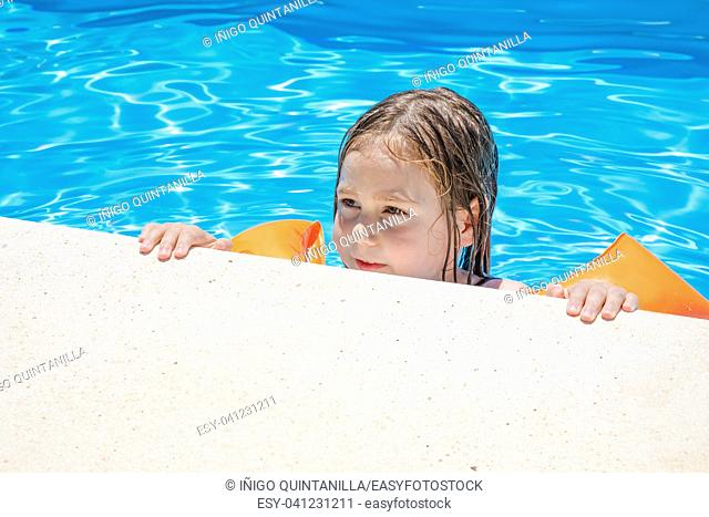 four years old blonde child with orange floater sleeves in arms, armbands, clinging or holding on to the curb of the swimming pool, with blue transparent water