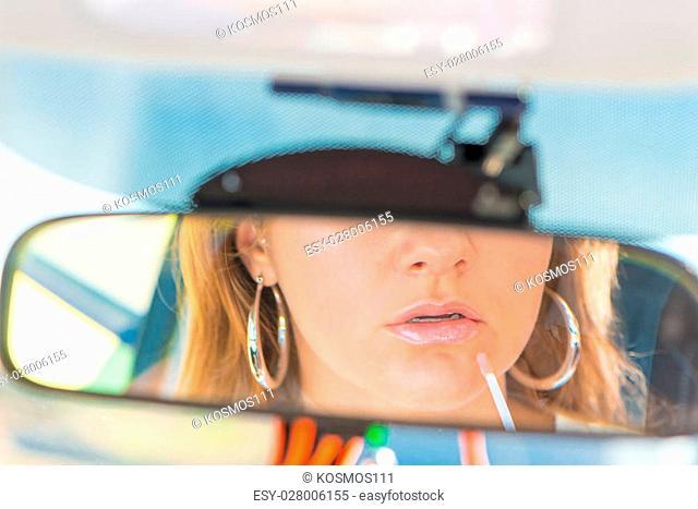 Car rearview mirror close-up girl applies lipstick
