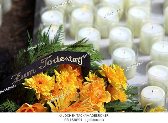 Lettering Zum Todestag, German for in commemoration of the anniversary of the death, a wreath of flowers on a grave, white candles