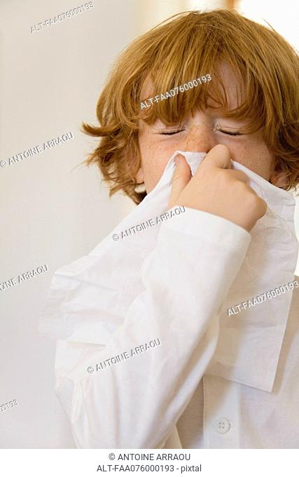 Boy blowing nose on tissue with eyes closed