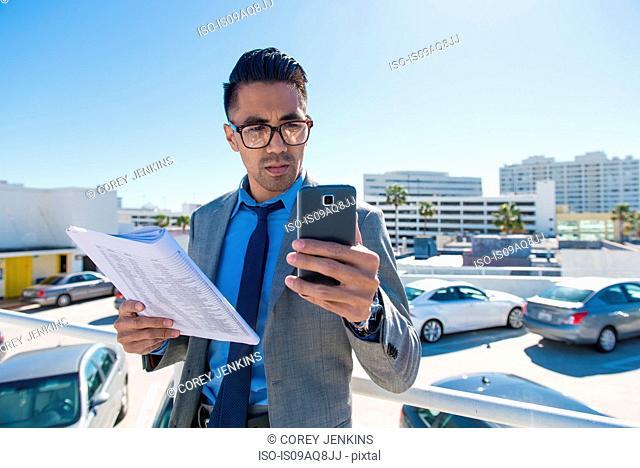 Young businessman on city rooftop car park reading smartphone texts