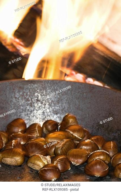 Chestnuts roasting in a pan on open fire, close up