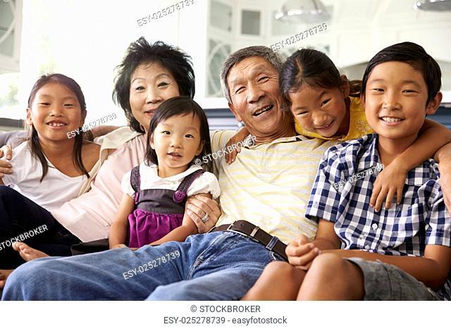 Portrait Of Grandparents With Grandchildren Sitting On Sofa