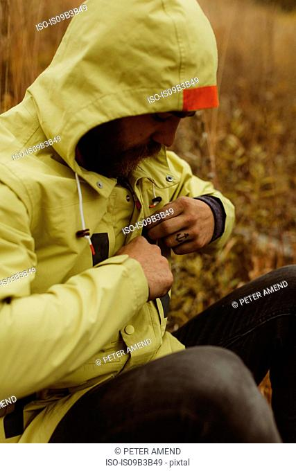 Male hiker fastening anorak, Mineral King, Sequoia National Park, California, USA