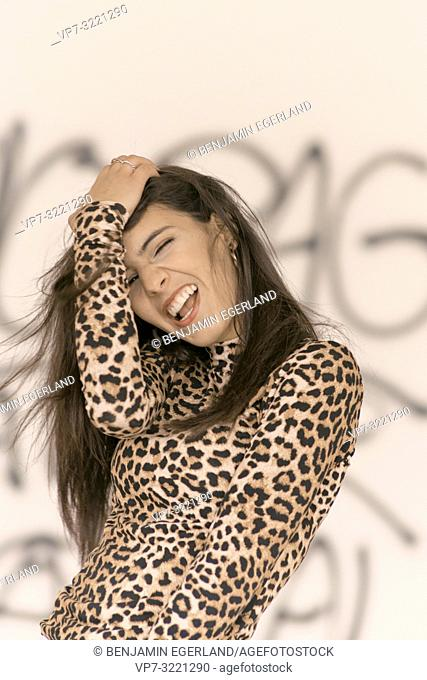 portrait of happy vibrant woman ruffling hair, wearing fashionable leopard print sweater, energised, in Munich, Germany