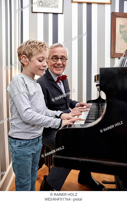 Grandfather and grandson playing piano together