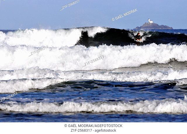 """Surfer on the waves of the """"""""baie des Trépassés"""""""" and the Tevennec lighthouse"""
