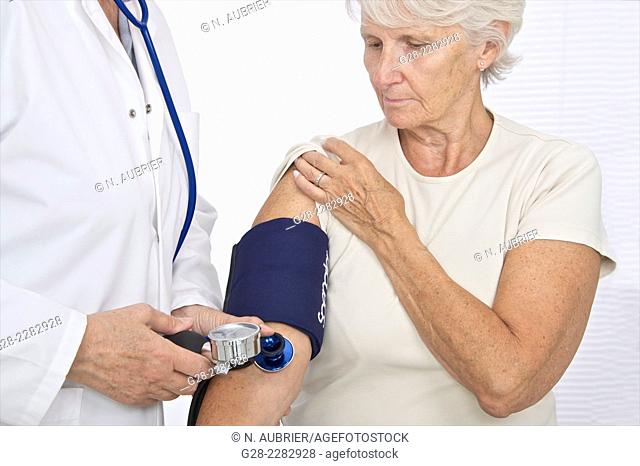 Senior woman having her blood pressure checked by a doctor