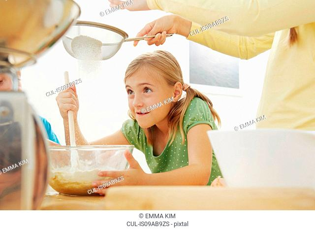 Children baking, sieving flour into mixing bowl