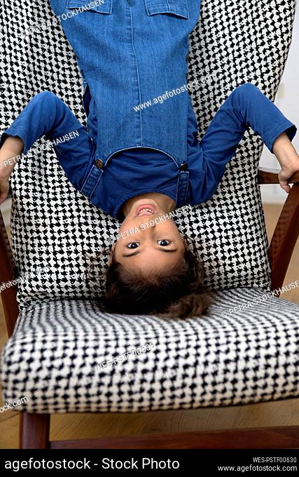 Portrait of little girl hanging upside down from backrest of an armchair