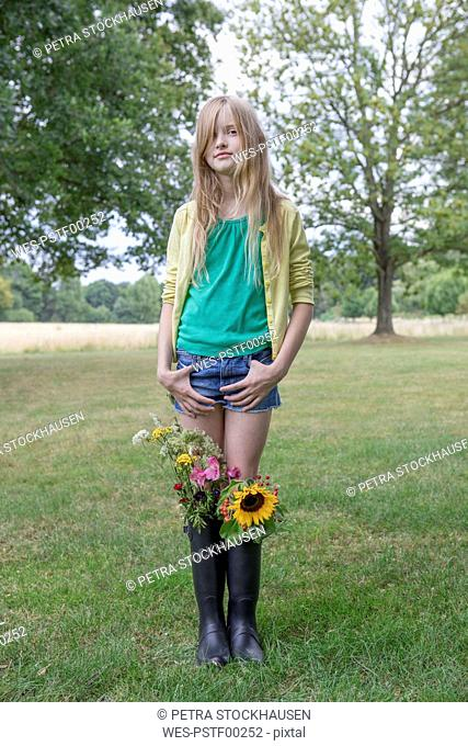 Portrait of blond girl standing on a meadow with bunches of flowers in her rubber boots