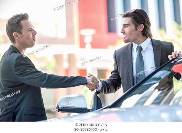 Two businessmen shaking hands in city