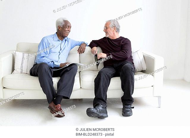Older men reading magazines sitting on sofa