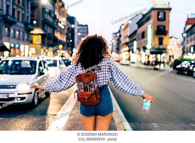 Woman in central reservation in street, Milan, Italy