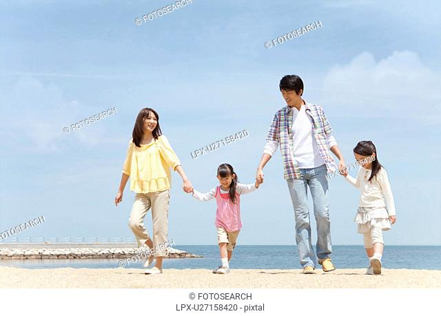 Family of Four Walking In Hand In Hand on Beach