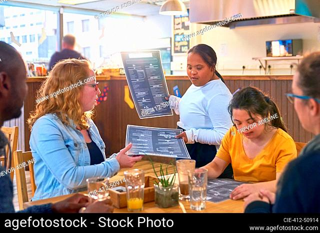 Young female server Down Syndrome giving menus to customers in cafe