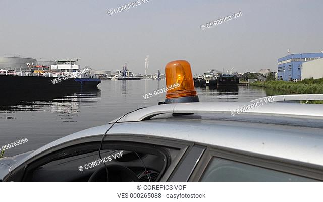 An orange flashlight on top of a car in an industrial harbor, zooming in