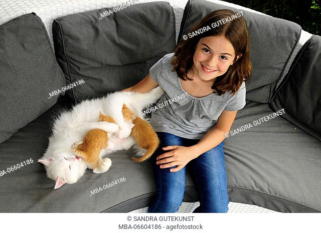Girls in jeans and grey T-shirt beside nursing cat on grey sofa, looking into camera