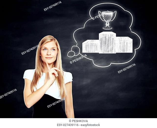 Beautiful businesswoman thinking about leadership on blackboard background