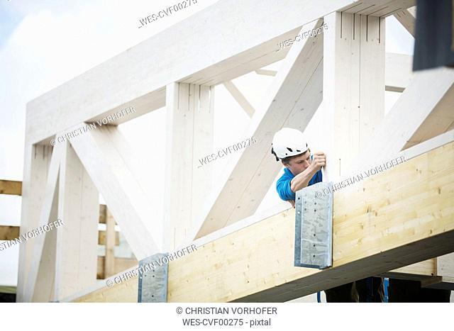 Austria, worker fixing roof construction