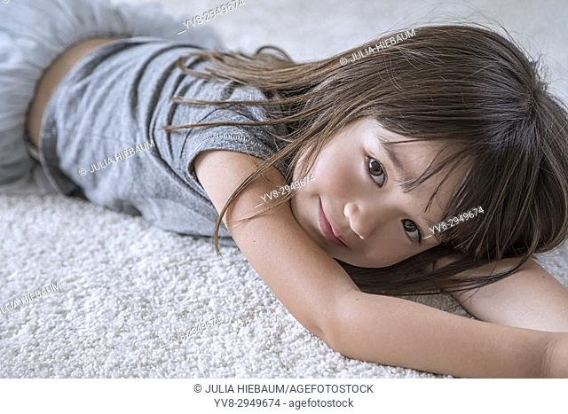 Five year old girl laying on the carpet in her room