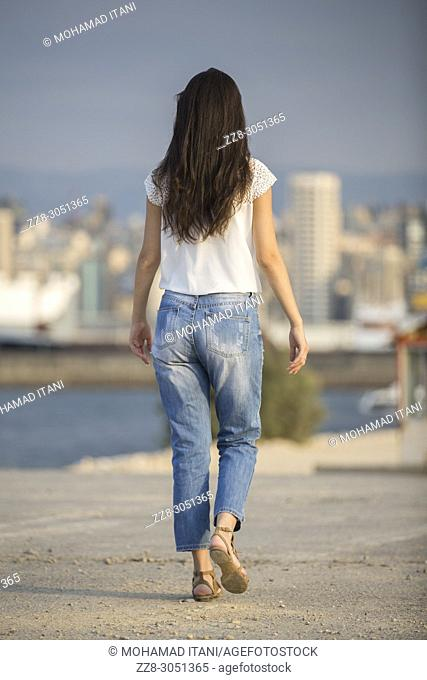 Rear view of a young woman walkign on the beach