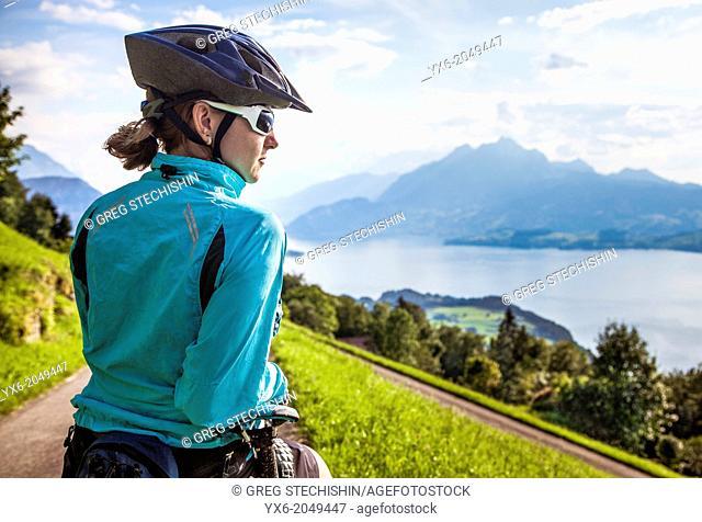 A woman taking a break while moutain biking in the area of Seebodenalp - Weggis on Mount Rigi in Switzerland
