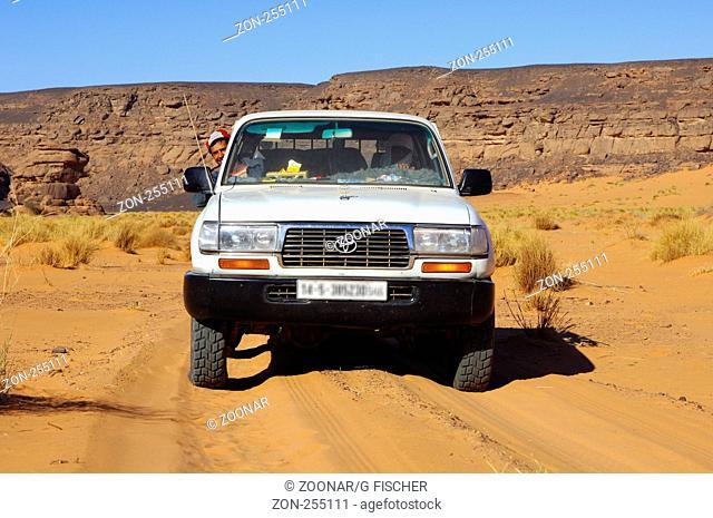 Jeep in Wüstenlandschaft, Akakus Gebirge, Libyen / Four-wheel drive jeep in a desert landscape, Acacus Mountains, Libya