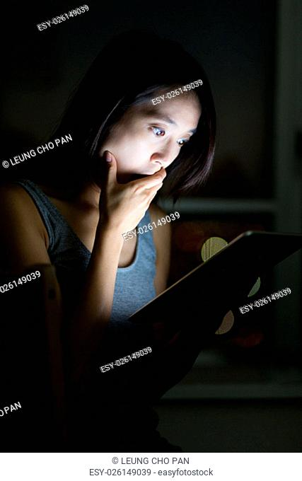 Asian Woman feeling shock when looking at the tablet