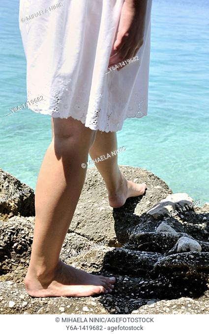 Young woman on rocks by ocean