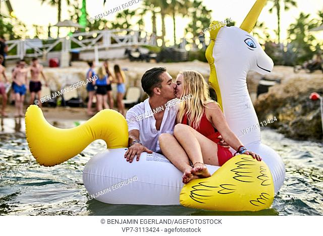 Greece, Crete, Chersonissos, couple at Beach Party sitting on inflatable, kissing, romantic