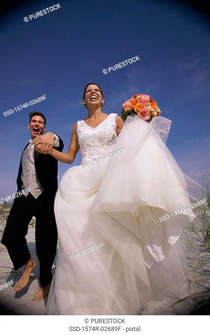 Low angle view of a newlywed couple running on sand