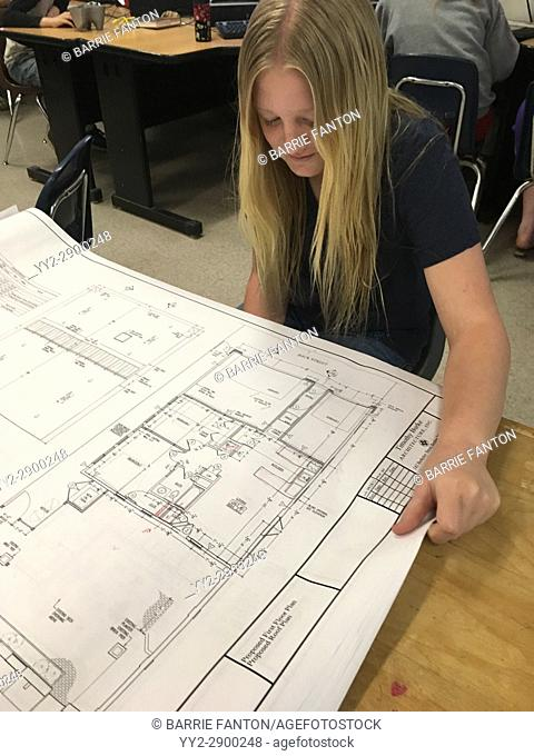 6th Grade Girl Looking at Architecture Plans, Wellsville, New York, USA