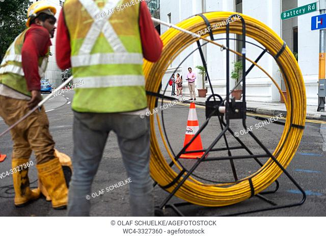 Singapore, Republic of Singapore, Asia - Two workers are laying cables on a road in the central business district