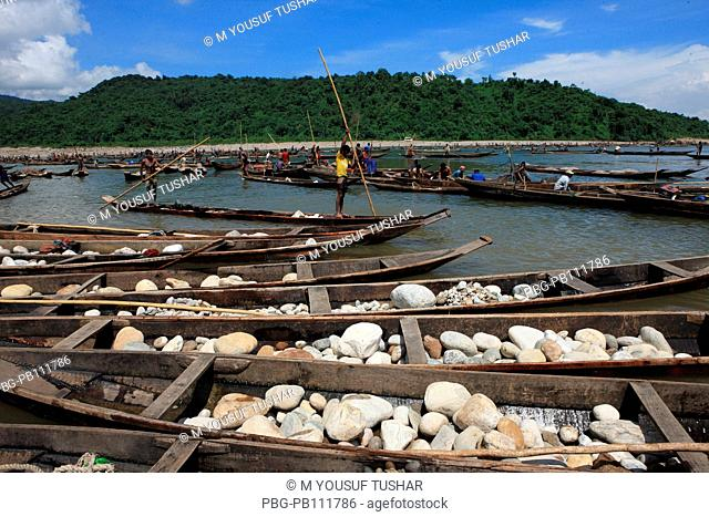 Stone workers collect stones in boats from the Dholai river in Bholaganj During monsoon season boulders, rocks, stones and pebbles wash up from India into the...