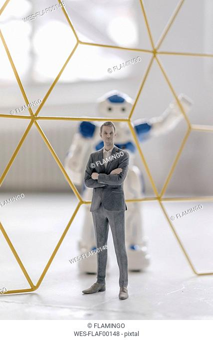 Miniature businessman figurine standing in front of robot seperated by structure