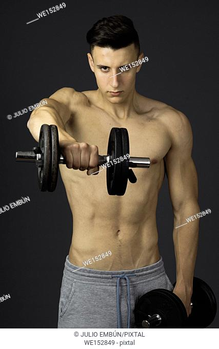 Young athletic and shirtless boy poses in the studio
