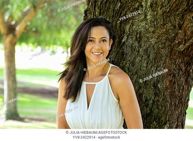 Smiling woman standing by a tree in Balboa park, San Diego, California