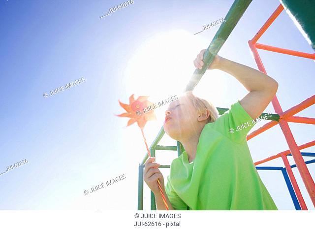 Boy blowing pinwheel on monkey bars at playground