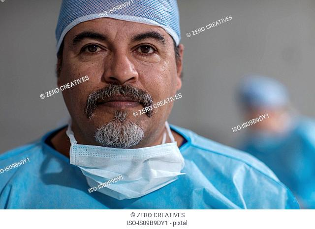 Portrait of male surgeon wearing scrubs and surgical mask